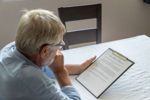 Senior old man elderly examining and checking last will and testament