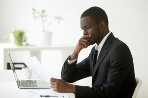 Man on his laptop with papers thinking about what to do